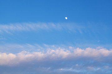 The moon in the sky in the daytime with the cloud against the blue sky background. Natural background