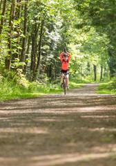 Happy, healthy, smiling woman having fun mountain biking. Women's outdoor adventure sports.