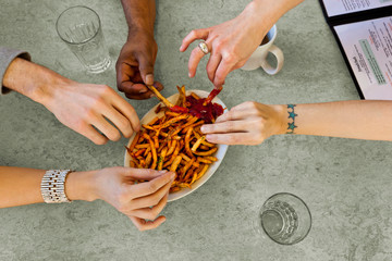 Overhead view of friends eating fries in restaurant