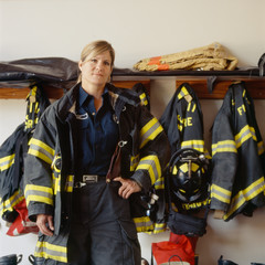 Portrait of female firefighter standing in fire station