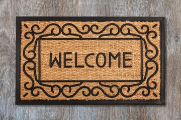 New welcome doormat on wooden floor