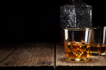 Two glass of whiskey with ice and crystal decanter on wooden table. Fototapete