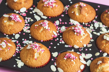 Muffins with sweet heart decor, pink background, paper heart with text I love you, Valentine's day
