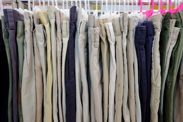 A row of many men's pants hanging on a clothes rank and selling in a shop