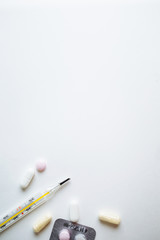 Pills for cold and mercury thermometer on a white background with space for text