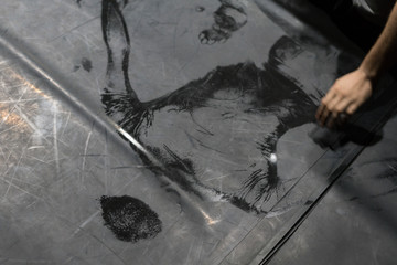 Scenic imprint of the dancer's back on a dark dance floor.
