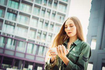 Young blond woman with smartphone in front of skyscrapers