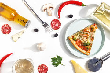 Slices of pizza, ingredients and cutlery on a white background. Top view.