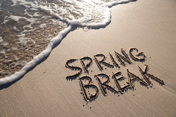 Spring Break message handwritten on the smooth sand of an empty beach with an oncoming wave