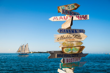 Bright scenic view of rustic wooden direction sign with sailboat in Key West, Florida, USA