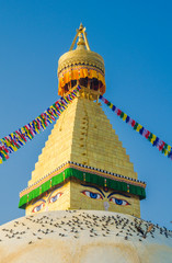 The dome and gold spire of Bodhnath Stupa, Kathmandu, Nepal, with Buddhist prayer flags.