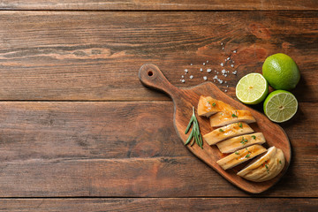 Board with fried chicken breast and limes on wooden background, top view. Space for text