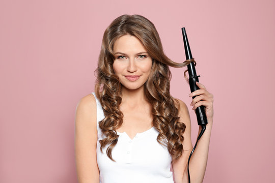 Portrait of young woman with shiny wavy hair using curling iron on color background