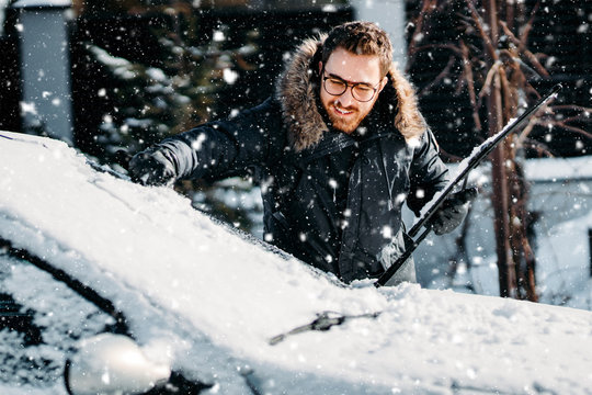 portrait of smiling man cleaning snow off his car during winter snowfall