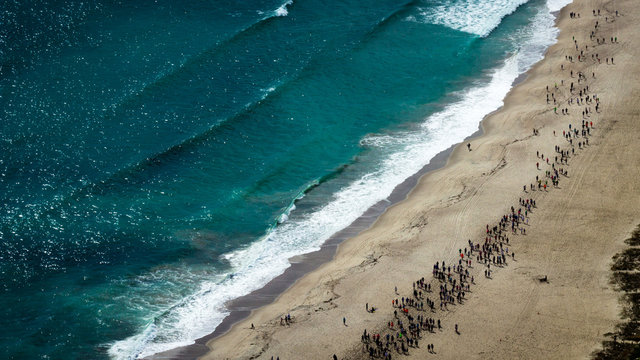 Hundreds of people running on the sand next to the waves of the Pacific Ocean. Aerial view of a marathon across the beach. From the top of Mount Maunganui Tauranga, Bay of Plenty. New Zealand.