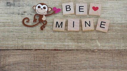 monkey holding a heart with block letters spelling be mine on a wood background with writing space