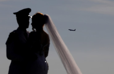 A newly married couple poses for a picture as a plane flies at Parque da Cidade in Brazil