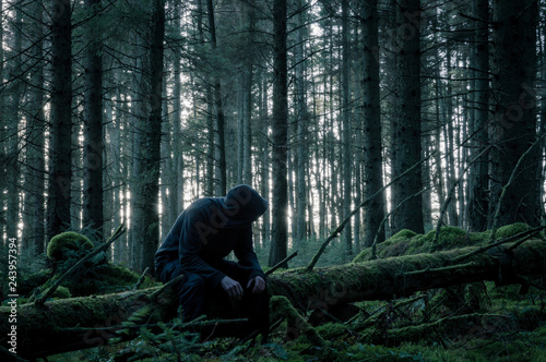 A spooky lone hooded figure sitting on a moss covered log in
