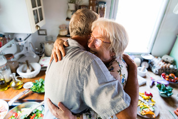 Cheerful senior people hugging in the kitchen