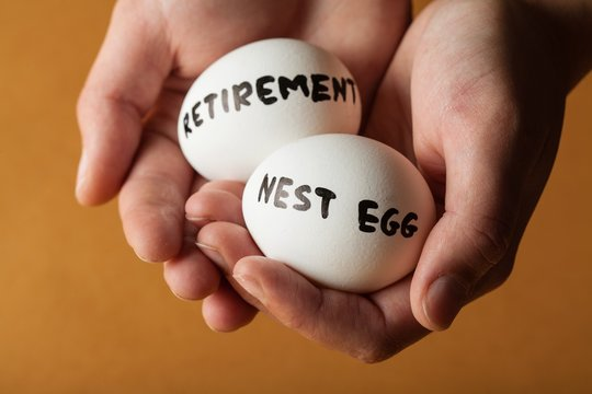 Hands Holding Two Eggs Marked Retirement And Nest Egg