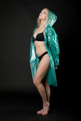 Young beautiful blond woman in underwear and a green raincoat in full growth. Photographing in a photo studio on a black background