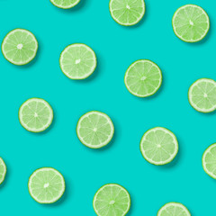 Fruit pattern of lime slices on blue background. Flat lay, top view.