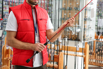Salesman with fishing rod in sports shop, closeup