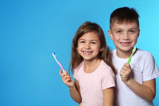 Portrait of cute children with toothbrushes on color background. Space for text