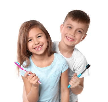 Portrait of cute children with toothbrushes on white background