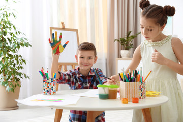 Little children painting hands at table indoors