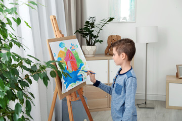 Little child painting picture using easel at home