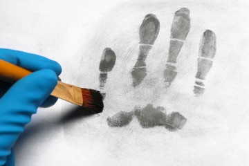 Criminalist taking fingerprints with brush from light surface, closeup. Forensic investigation