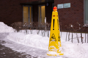 Obraz Caution Wet Floor. Slippery Yellow Surface Sign On Red Brick Building And Snow Heap. Slippery Slope. Icing Concept: Be Aware Of Slippery Road And Watch Your Step, Please. - fototapety do salonu