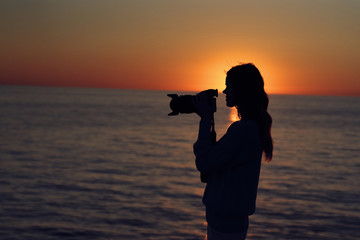 silhouette woman with camera sea sunset