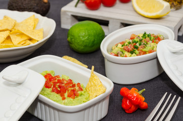 Guacamole and salsa dip next to tortilla chips. A delicious bowl of guacamole next to fresh ingredients on a table with tortilla chips and salsa.