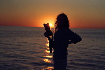 sunset woman with camera silhouette sea