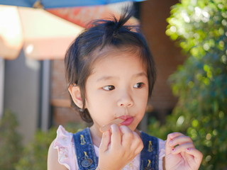 Little Asian baby girl, 36 months old, enjoys putting a stick into her mouth even after she has eatten all of the ice cream
