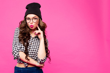 Beautiful young woman with bright makeup and pink lips make a kiss holding your finger near the lips. Hipster girl in hat isolated on pink background in Studio.
