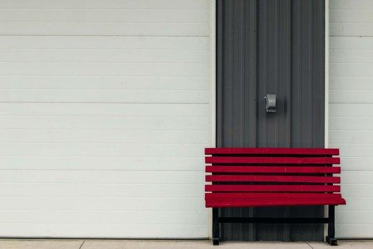 red bench in front of white garage with grey walls