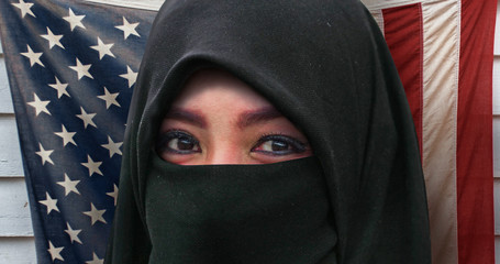beautiful face of Muslim woman in traditional Islam burqa or burka head scarf posing cheerful and happy smiling isolated on United States American flag background