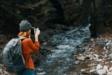 woman photographing a river in the woods trip