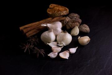 Garlic and dry bael fruit tea and Mushroom, cinnamon, Star anise isolated on black background