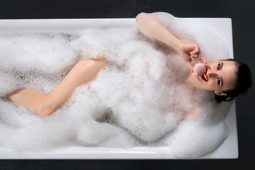 Happy brunette having bath high angle shot
