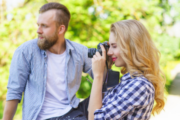 Man and woman having date outdoor. Girl wit a photo camera and her boyfriend.