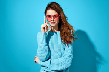 woman wearing glasses in a sweater on a blue background