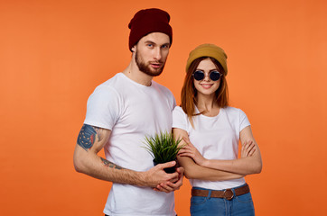 young couple in white t-shirt hats on orange background