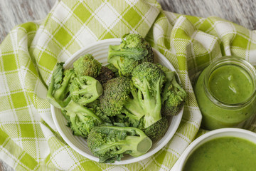 Fresh broccoli in the bowl, and portion of puree made from crushed broccoli, blurred background