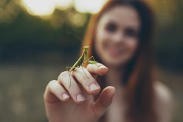 grasshopper close up on woman hand