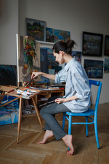 A young woman artist sits in a bright studio on a blue chair and paints a picture in oil on the easel. The woman loose comfortable casual clothing. Vertical photo.