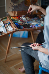 A woman paints on canvas with a brush and paints in her art studio. The frame is only a woman's hand.
